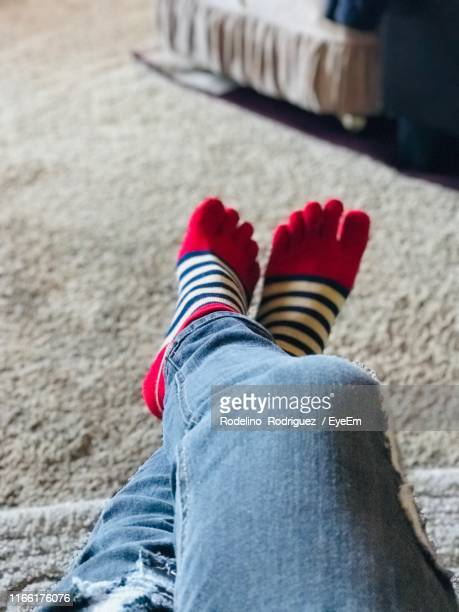 low section of person wearing socks on floor at home - legs crossed at ankle stock pictures, royalty-free photos & images