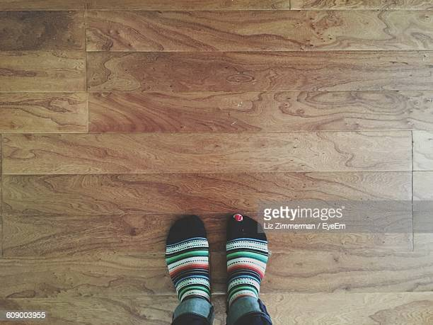 Low Section Of Person Wearing Socks On Hardwood Floor At Home