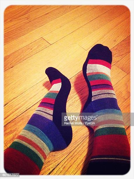 low section of person wearing socks while sitting on floorboard - rachel wolfe stock pictures, royalty-free photos & images