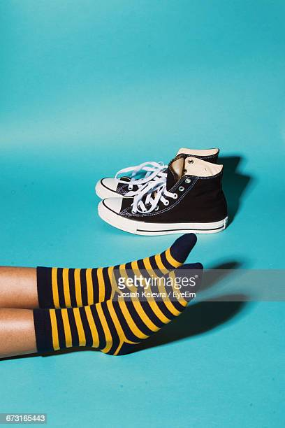 low section of person wearing striped socks on blue background - sock stock pictures, royalty-free photos & images