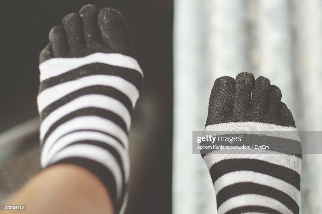 Low Section Of Person Wearing Striped Socks : Photo