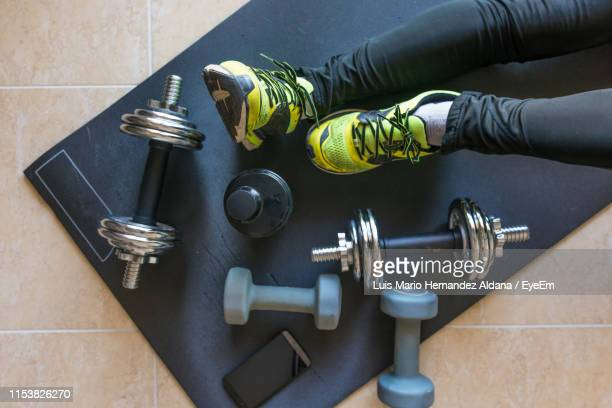 low section of person with dumbbells and phone in gym - dansstudio stock pictures, royalty-free photos & images