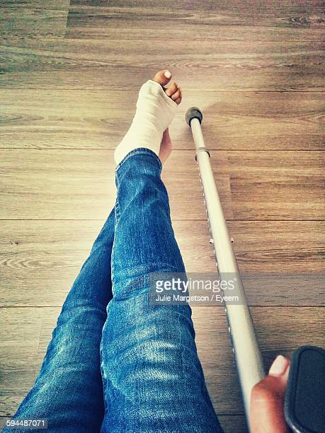 low section of person with fractured leg holding crutch - pierna fracturada fotografías e imágenes de stock