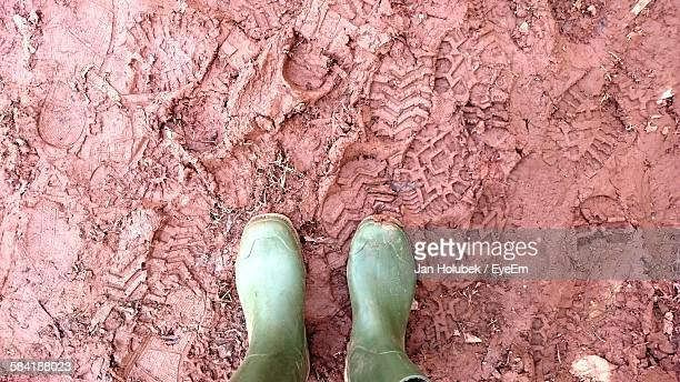 Low Section Of Person With Green Rubber Boots Standing On Mud