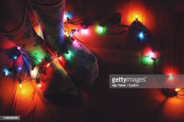 low section of person with illuminated string lights during christmas at home - low section stock pictures, royalty-free photos & images