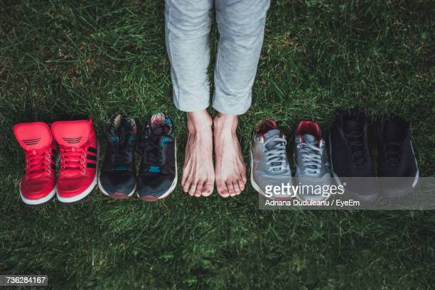 Low Section Of Person With Shoe Collection On Grass