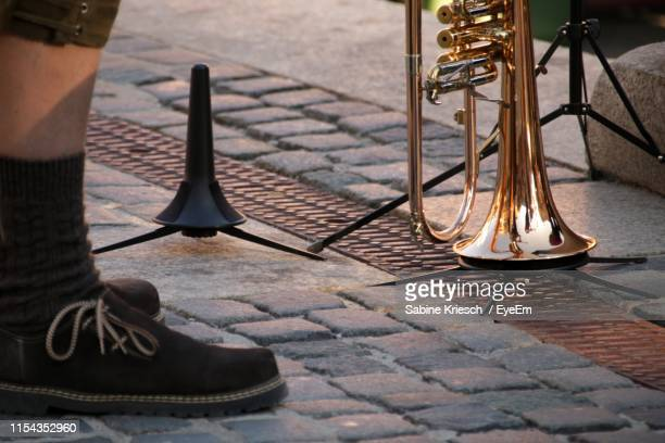 low section of person with trumpet on footpath - sabine kriesch stock-fotos und bilder