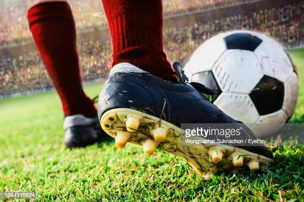 low section of player kicking soccer ball on field - football fotografías e imágenes de stock