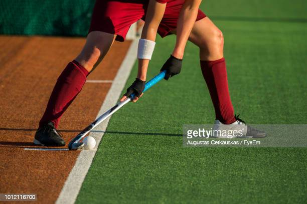 low section of player playing hockey on field - hockey stock pictures, royalty-free photos & images