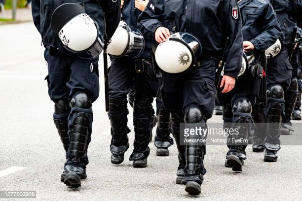 low section of police force walking on street - beschützer stock-fotos und bilder