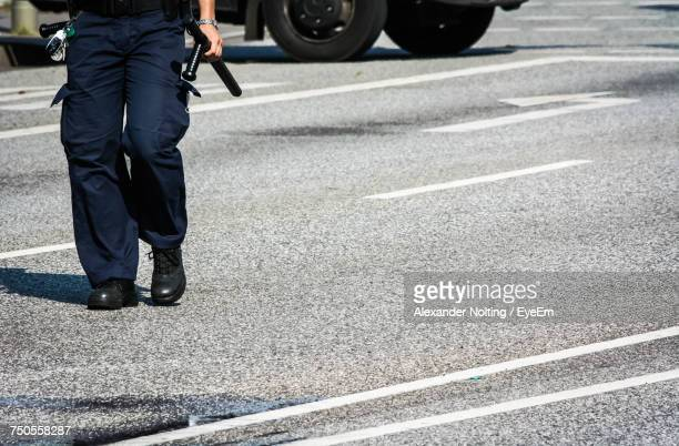 Low Section Of Police Officer Walking On Street