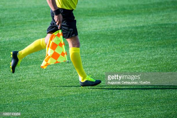 low section of referee with flag running on soccer field - referee stock pictures, royalty-free photos & images