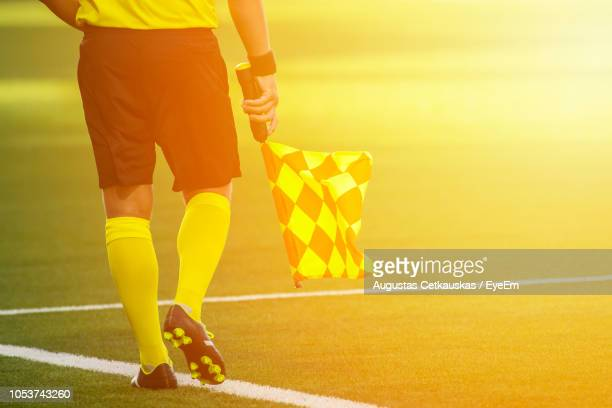 low section of referee with flag walking on soccer field - soccer referee stock photos and pictures