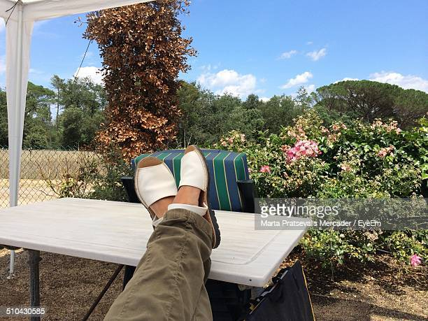 Low section of relaxed woman with feet up on table outdoors