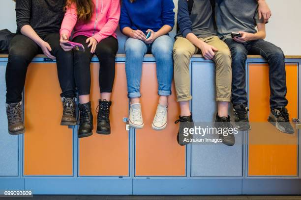 Low section of schoolchildren (12-13) sitting on lockers