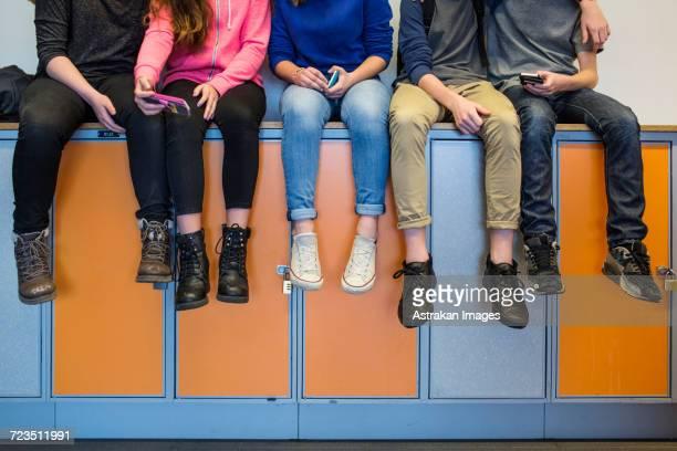 Low section of schoolchildren sitting on lockers
