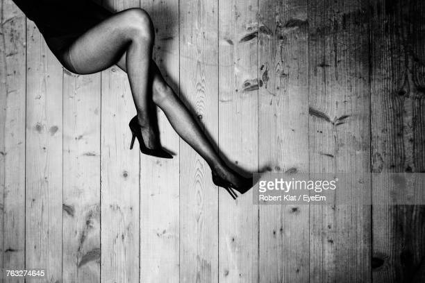 low section of seductive woman lying on hardwood floor - sexy girls stock pictures, royalty-free photos & images