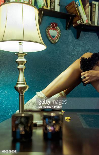 Low Section Of Seductive Woman Removing Stockings On Table At Home