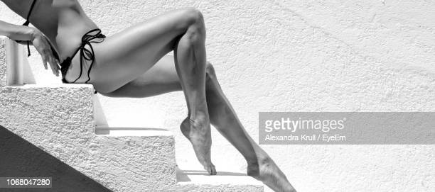 Low Section Of Seductive Woman Sitting On Steps Against White Wall
