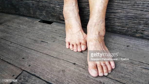 low section of senior man standing on wooden plank - barefoot stock pictures, royalty-free photos & images