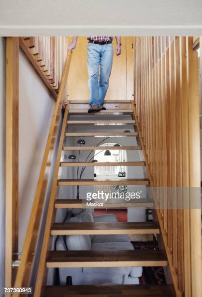 Low section of senior man walking down wooden steps at home