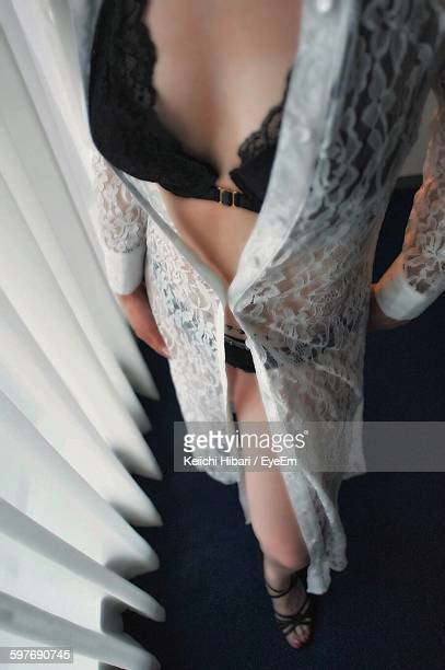Low Section Of Sensuous Woman Wearing Lingerie Standing By Curtains