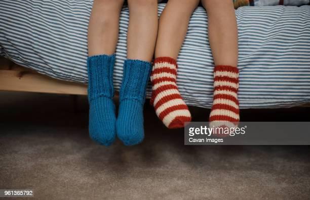 low section of siblings sitting on bed at home - onderste deel stockfoto's en -beelden