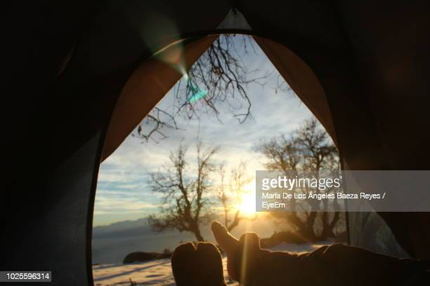 Low Section Of Silhouette Person Relaxing In Tent Against Sky During Sunset