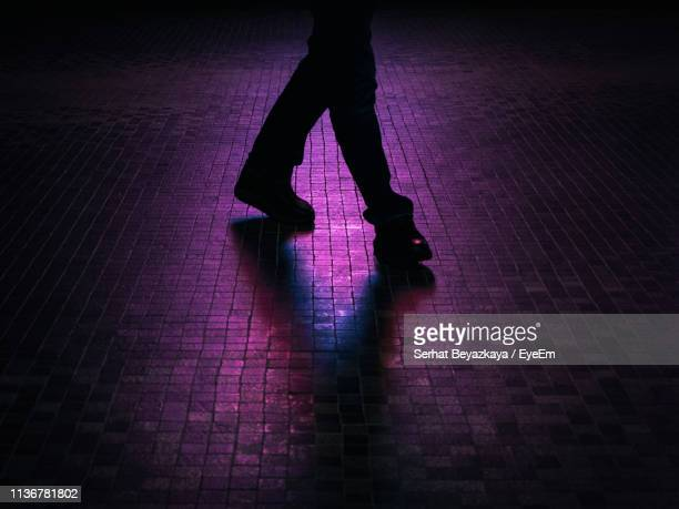 low section of silhouette person walking on footpath at night - purple shoe stock pictures, royalty-free photos & images