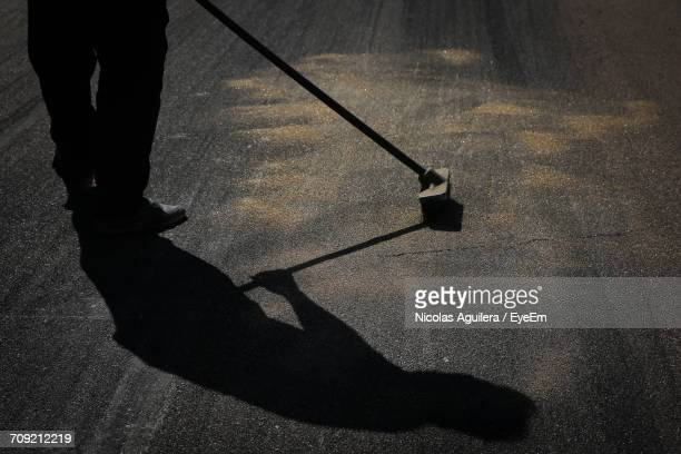 Low Section Of Silhouette Worker Sweeping Road