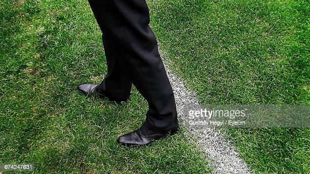Low Section Of Soccer Coach Standing On Grassy Field