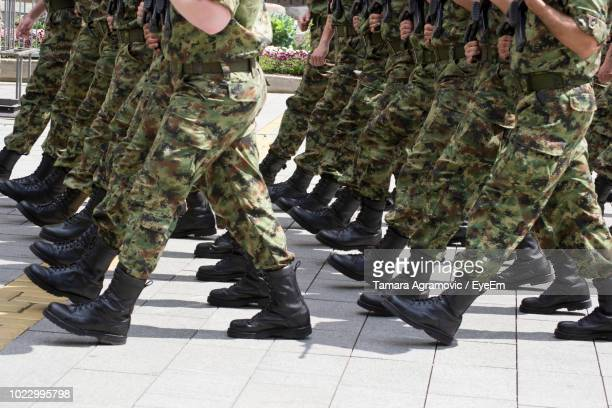 low section of soldiers marching on street - marching stock pictures, royalty-free photos & images