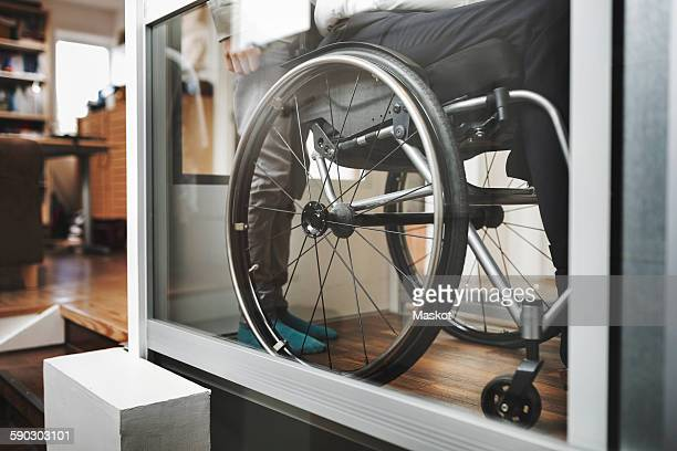 low section of son and father in wheelchair lift at home - disabled access stock photos and pictures