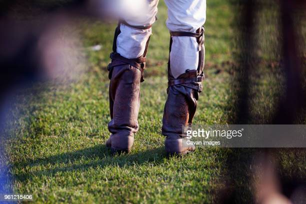 low section of sportsman standing on grassy field - riding boot stock pictures, royalty-free photos & images