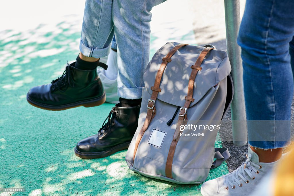 Low section of students by backpack at campus : Stock Photo