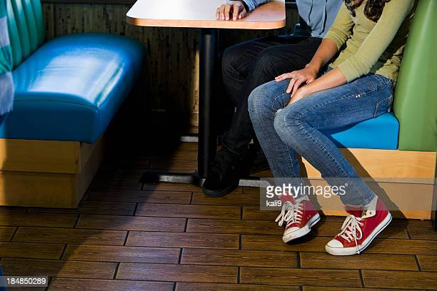 Low section of teenage couple sitting in restaurant booth