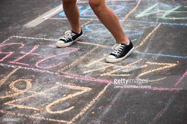 low section of teenage girl playing outdoors - hopscotch stock photos and pictures