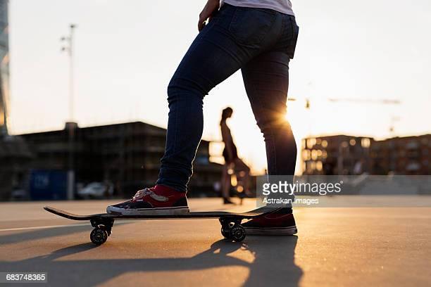 Low section of teenage girl skateboarding in skate park during sunset