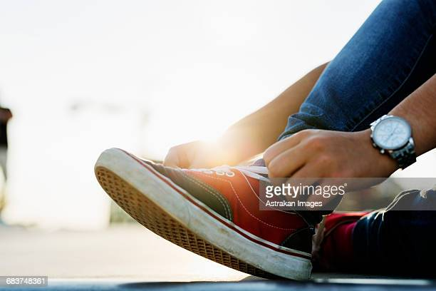 Low section of teenage girl tying shoe lace at skate park