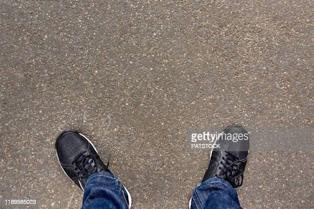 low section of teenager standing on asphalt road - low section stock pictures, royalty-free photos & images