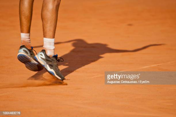 low section of tennis player playing on field during sunny day - tennis photos et images de collection