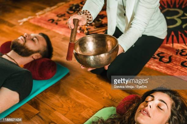 low section of therapist playing rin gong by couple while performing music therapy at spa - rin gong stock pictures, royalty-free photos & images