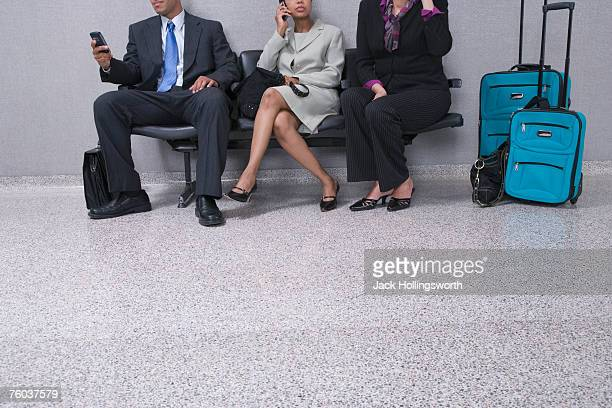 Low section of three business people with suitcases using mobile phones