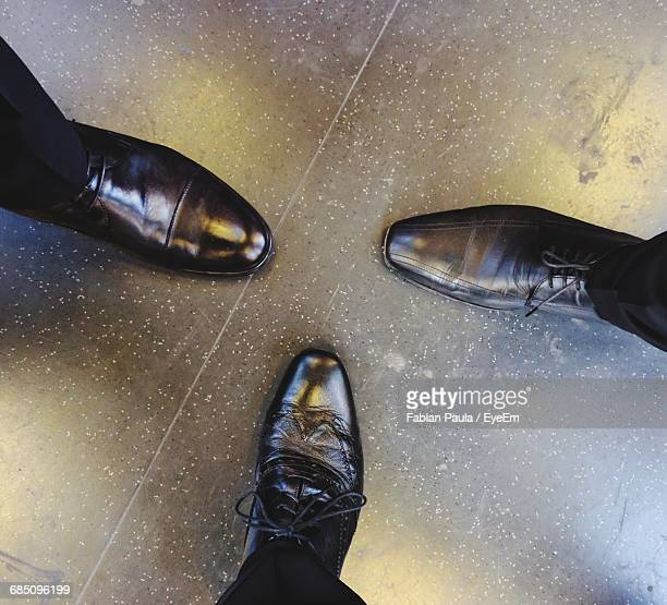 Low Section Of Three Men Wearing Black Shoes