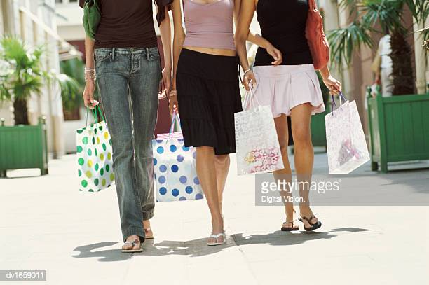 low section of three teenage girls walking towards the camera holding shopping bags - girl wear jeans and flip flops stock photos and pictures
