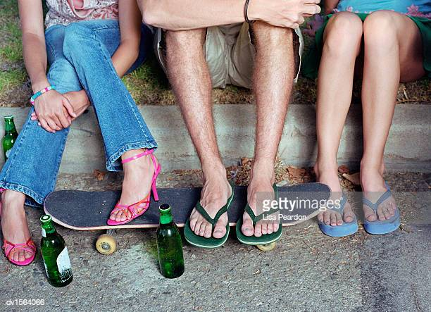 low section of three teenagers sitting on a curb, skateboard and empty beer bottles on the pavement by their feet - girl wear jeans and flip flops stock photos and pictures