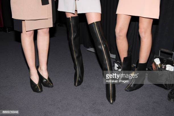 low section of three women wearing skirts and black leather high heels - ブーツ ストックフォトと画像