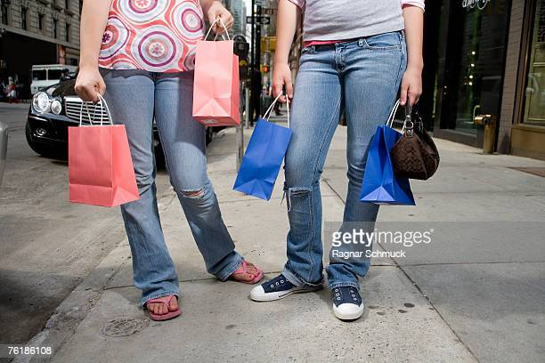 Low section of two adolescent girls holding shopping bags and standing on a sidewalk