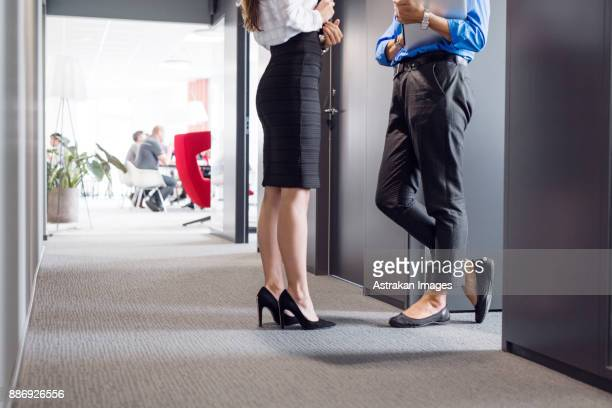 low section of two architects talking in corridor - up skirts stock pictures, royalty-free photos & images