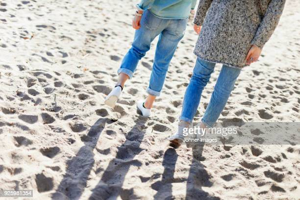 Low section of two girls walking on sand